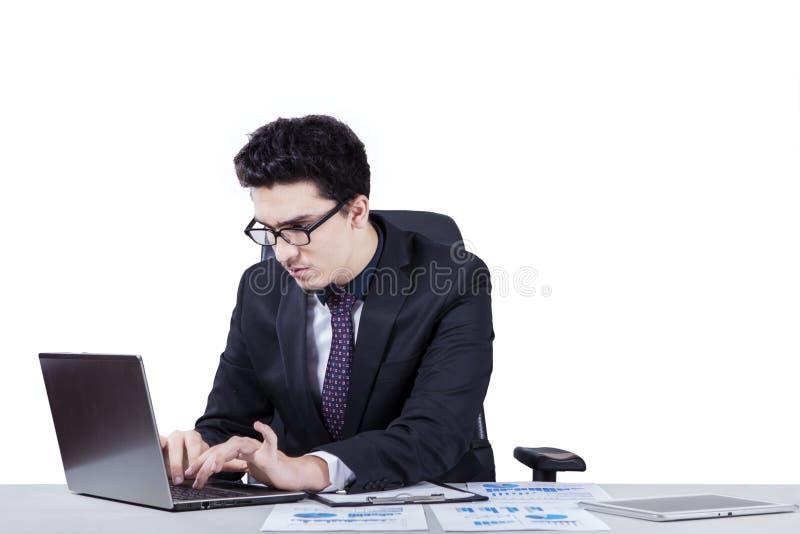 Мужской бухгалтер работая с компьтер-книжкой на столе стоковые фото