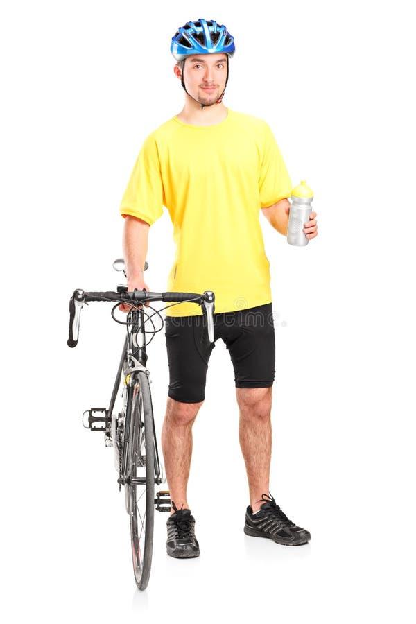Мужской велосипедист держа бутылку с водой стоковое фото rf
