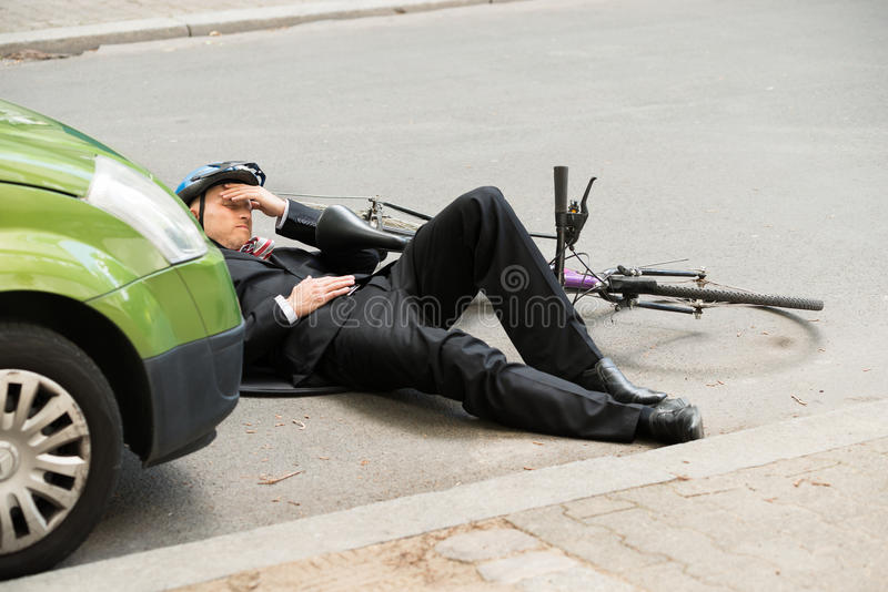 Мужской велосипедист после автомобильной катастрофы на дороге стоковое фото rf