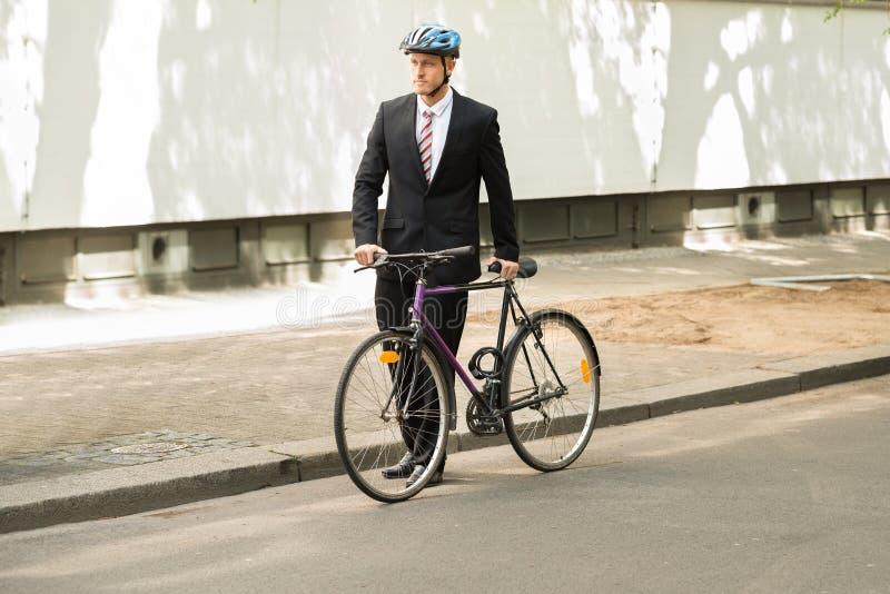 Мужской велосипедист с его велосипедом на дороге стоковые изображения rf