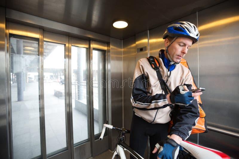 Мужской велосипедист с сумкой курьера используя мобильный телефон стоковые изображения rf