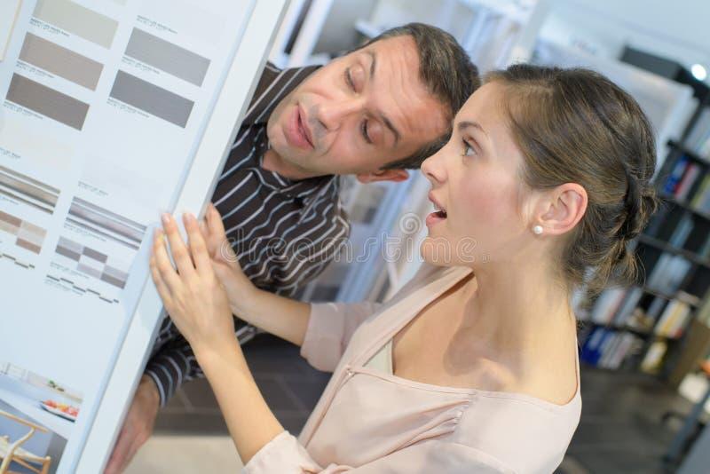 Мужской внутренний оформитель советуя клиенту на цветах краски стоковые изображения