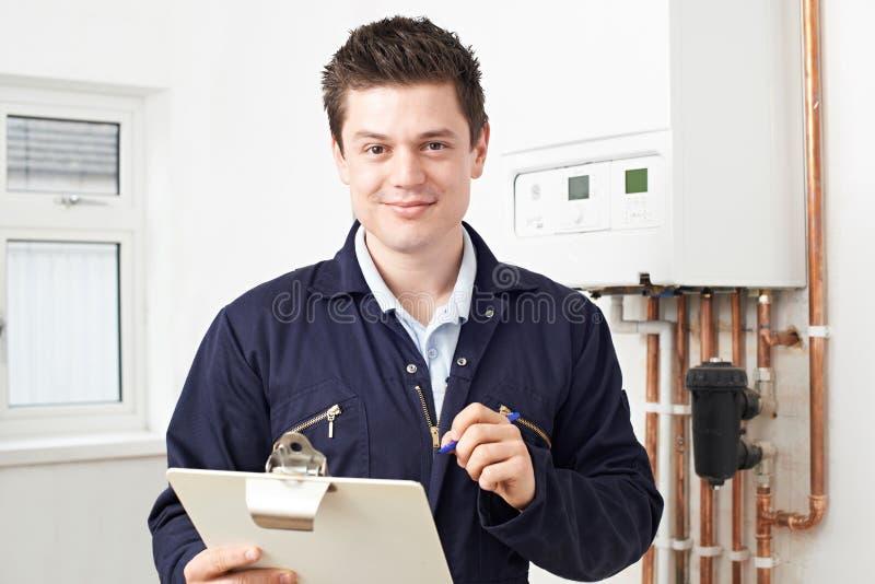 Мужской водопроводчик работая на боилере центрального отопления стоковое фото rf