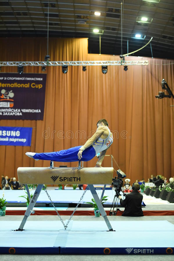 Мужской гимнаст выполняя на лошади луки стоковые изображения