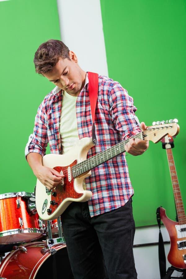 Мужской гитарист выполняя в студии звукозаписи стоковое фото