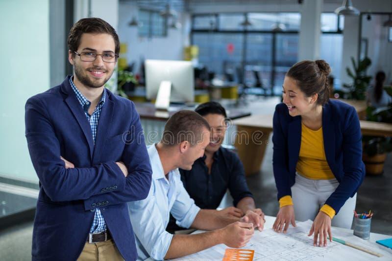Мужской график-дизайнер усмехаясь пока коллега взаимодействуя над светокопией в предпосылке стоковые изображения rf