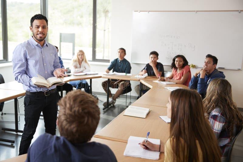 Мужской гувернер средней школы при зрачки сидя на классе математик таблицы уча стоковое фото rf