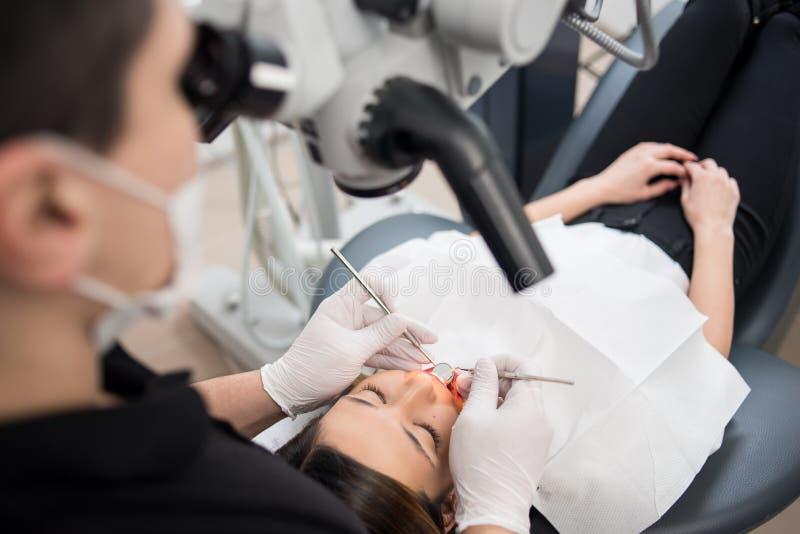 Мужской дантист с зубоврачебными инструментами - микроскопом, зеркалом и зондом проверяя вверх по терпеливым зубам на зубоврачебн стоковое фото