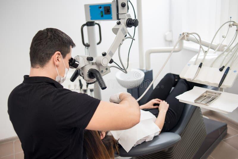 Мужской дантист с зубоврачебными инструментами - микроскопом, зеркалом и зондом обрабатывая терпеливые зубы на зубоврачебном офис стоковое фото