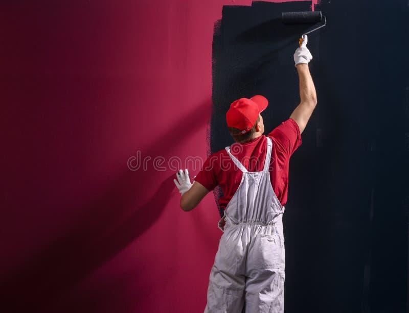 Мужской декоратор рисует стену черным цветом стоковое изображение rf