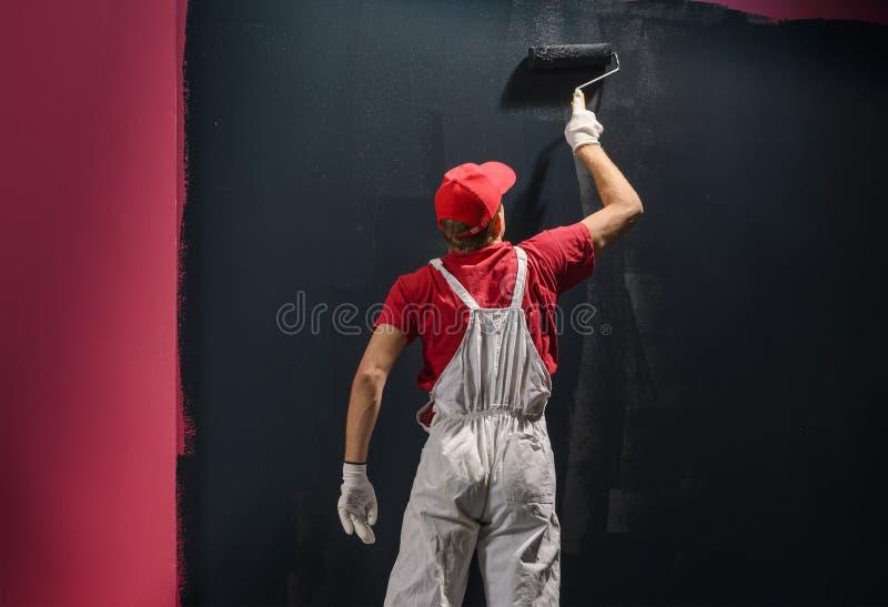 Мужской декоратор рисует стену черным цветом стоковое фото rf