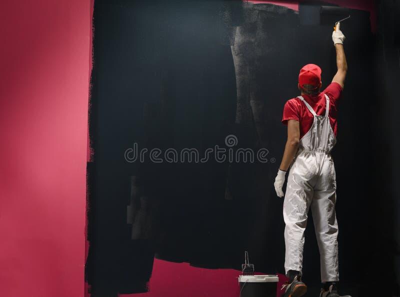 Мужской декоратор рисует стену черным цветом стоковые изображения