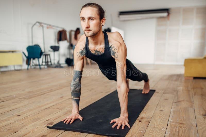 Мужской делать йоги нажимает вверх тренировку стоковые фотографии rf