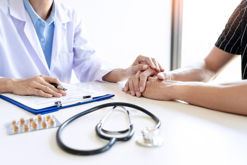 Мужской доктор держа руку пациента, утешающ пациента который в машине скорой помощи, помогая концепции стоковая фотография rf