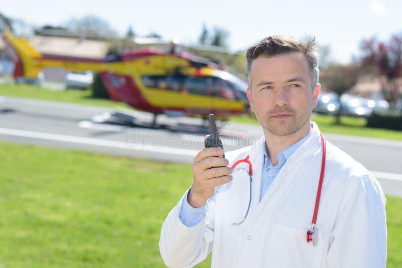 Мужской доктор держа walkie звукового кино близко спасает вертолет стоковое изображение