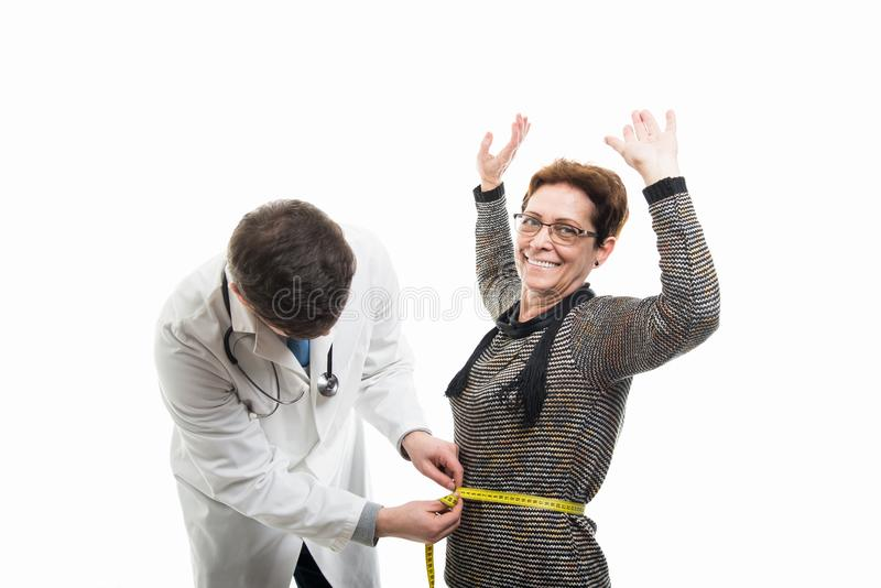 Мужской доктор измеряя счастливого женского старшего пациента стоковое изображение rf