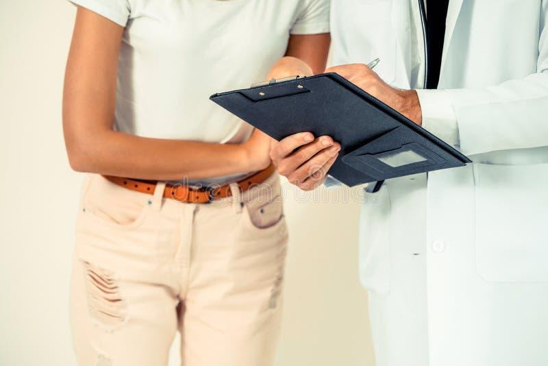 Мужской доктор и женский пациент в офисе больницы стоковое изображение rf