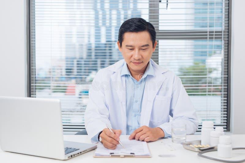 Мужской доктор работая на столе в комнате ` s доктора стоковое изображение rf