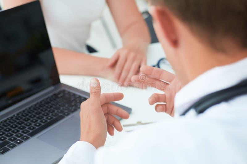 Мужской доктор советует с с женским пациентом о ее здоровье на работая столе который используя компьтер-книжку технологии на боль стоковые фото