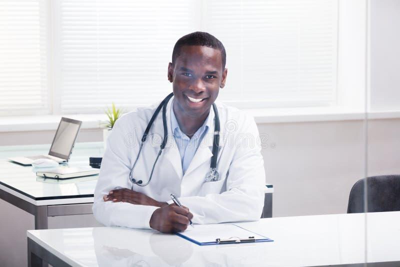 Мужской доктор С Доска сзажимом для бумаги и ручка сидя в клинике стоковые фото
