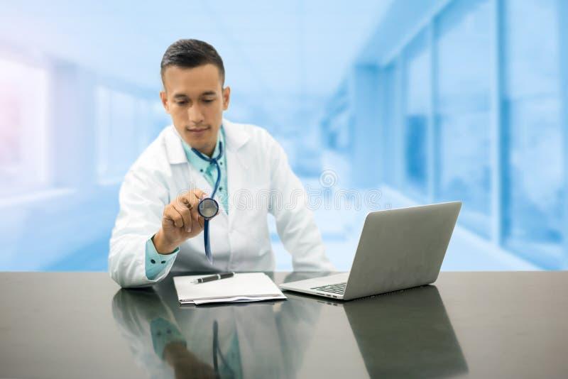Мужской доктор Working на столе офиса в больнице стоковые фотографии rf