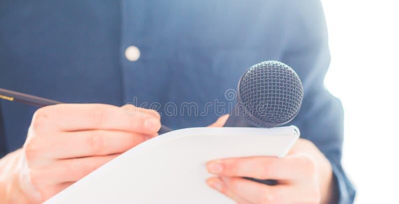 Мужской журналист на пресс-конференции, держа микрофон и принимая примечания стоковое фото rf