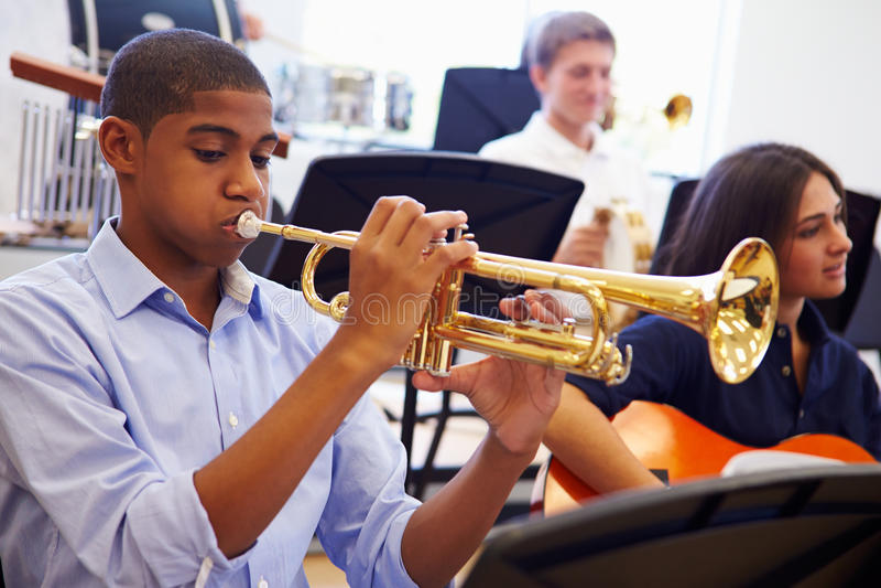 Мужской зрачок играя трубу в оркестре средней школы стоковое фото rf