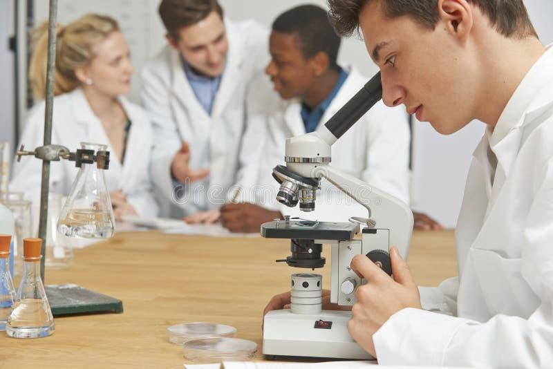 Мужской зрачок используя микроскоп в классе науки стоковая фотография rf