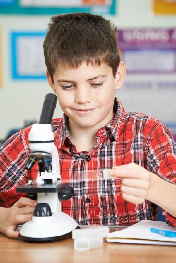 Мужской зрачок используя микроскоп в уроке науки стоковое изображение rf