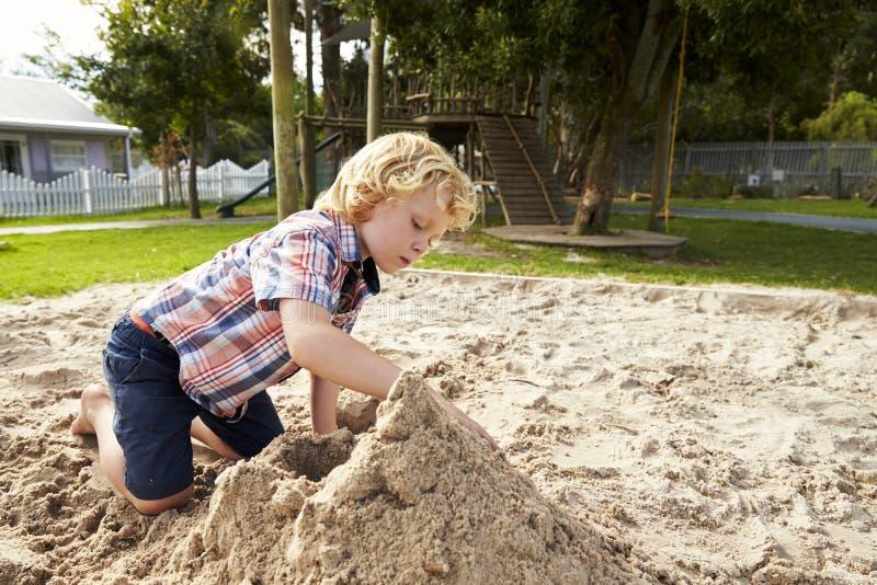 Мужской зрачок на школе Montessori играя в яме песка на Breaktime стоковые изображения rf