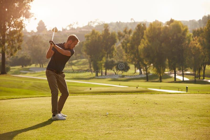 Мужской игрок в гольф выравнивая вверх тройник снятый на поле для гольфа стоковое изображение