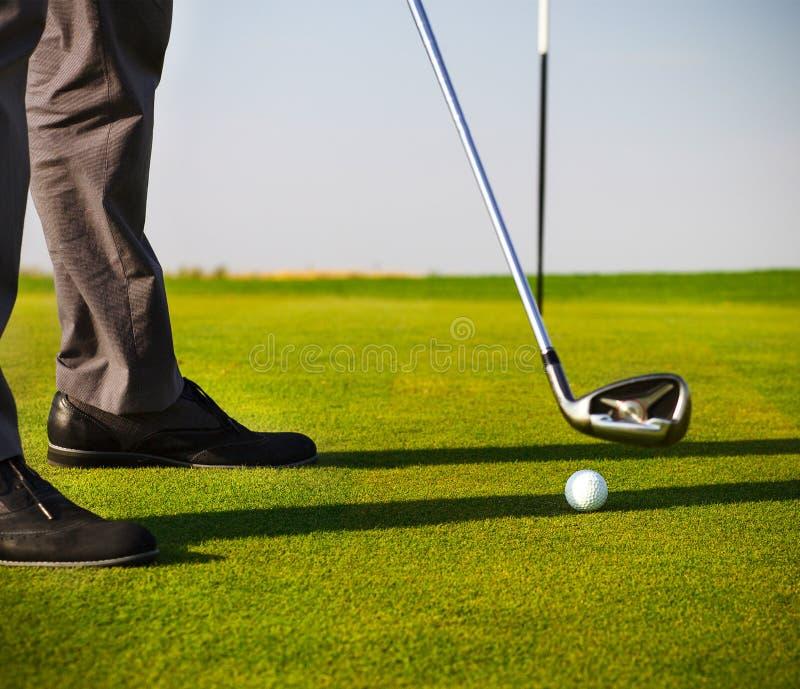 Мужской игрок в гольф кладя, фокус на шаре для игры в гольф стоковая фотография