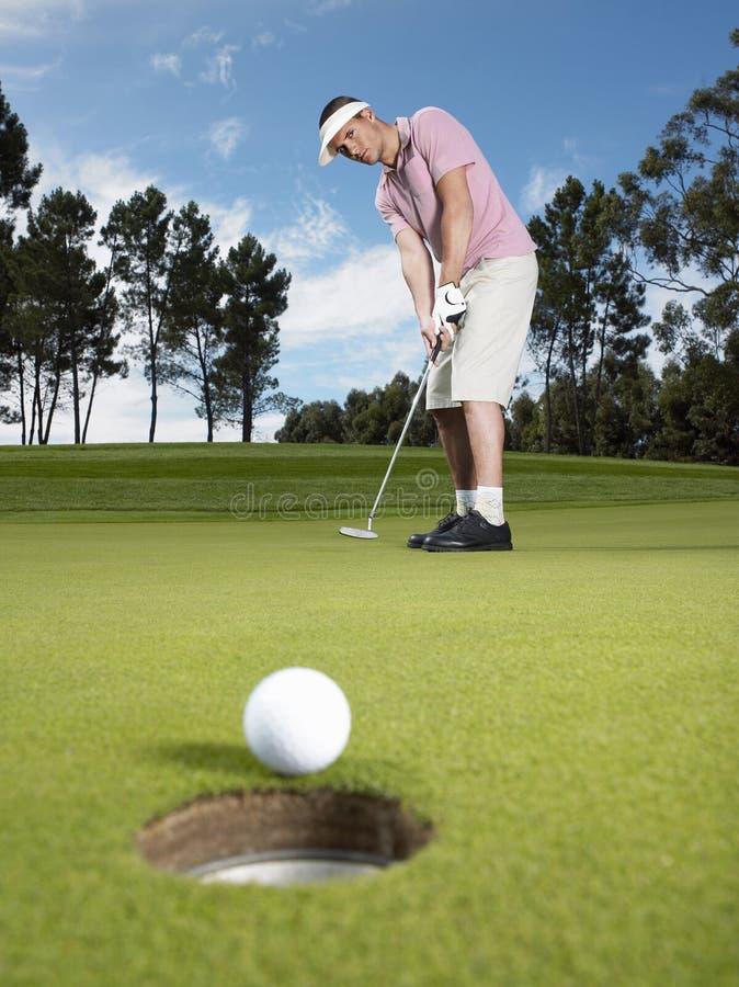 Мужской игрок в гольф кладя шарик на зеленый цвет стоковое фото