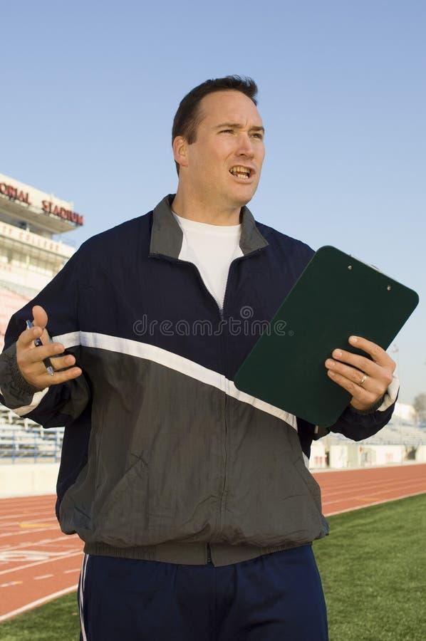 Мужской инструктор держа доску сзажимом для бумаги стоковое изображение rf