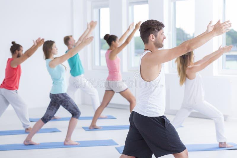 Мужской инструктор фитнеса с студентами стоковое изображение rf