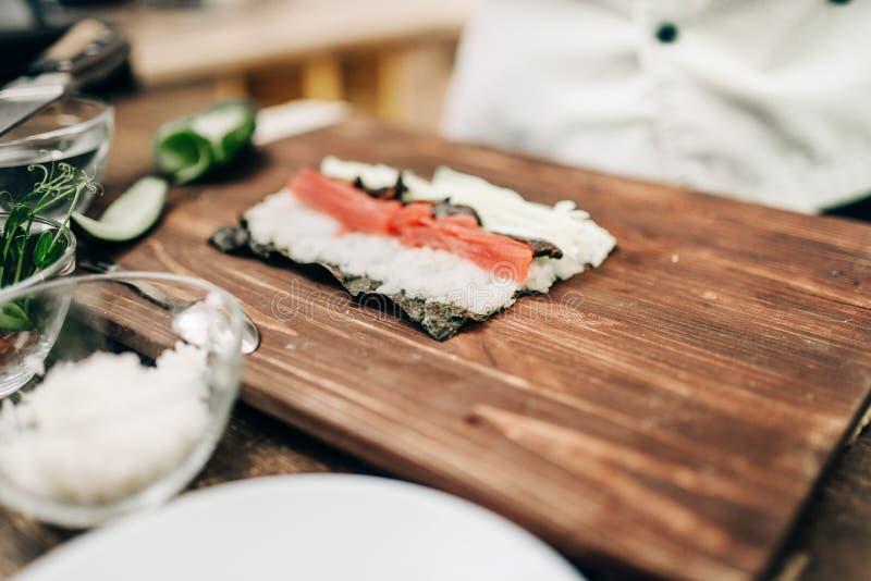 Мужской кашевар делая суши на деревянном столе, взгляд сверху стоковое фото