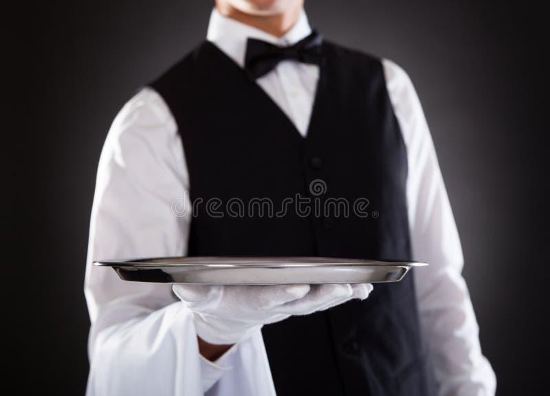 Мужской кельнер держа поднос стоковые изображения