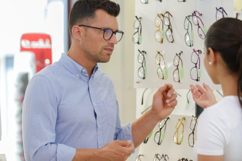 Мужской клиент выбирая стекла в магазине оптики стоковые изображения rf