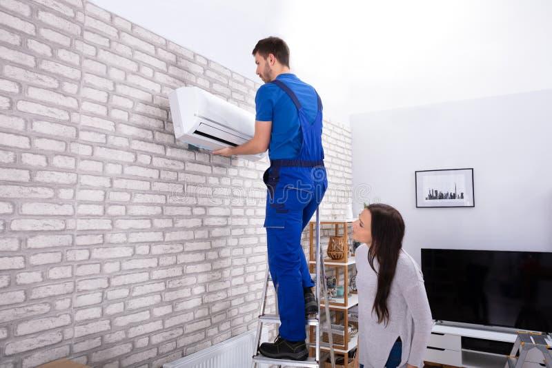 Мужской кондиционер отладки техника на стене стоковое изображение