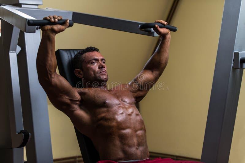 Мужской культурист делая тяжеловесную тренировку для верхнего комода стоковое фото rf