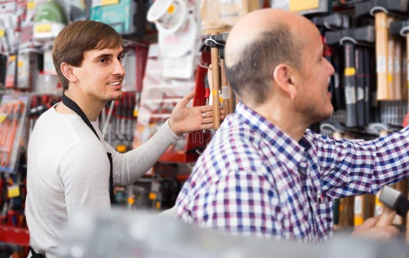 Мужской клиент и молодой продавец на разделе tooling стоковое изображение