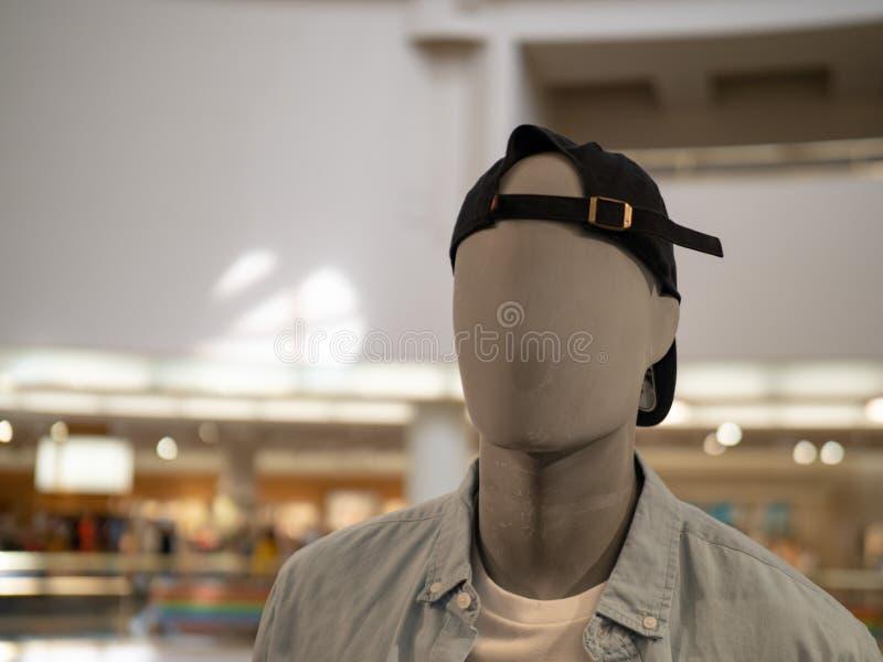Мужской манекен с ОН назад бейсбольной кепкой в универмаге стоковая фотография rf