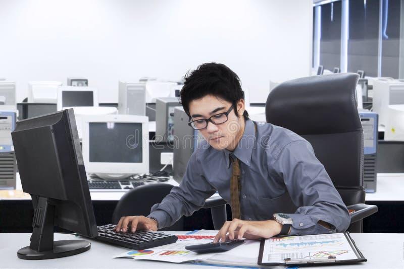 Мужской менеджер делая его работу в офисе стоковые изображения
