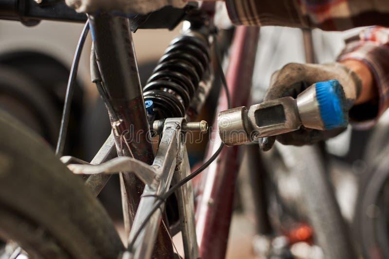 Мужской механик работая в ремонтной мастерской велосипеда используя инструменты стоковые фото
