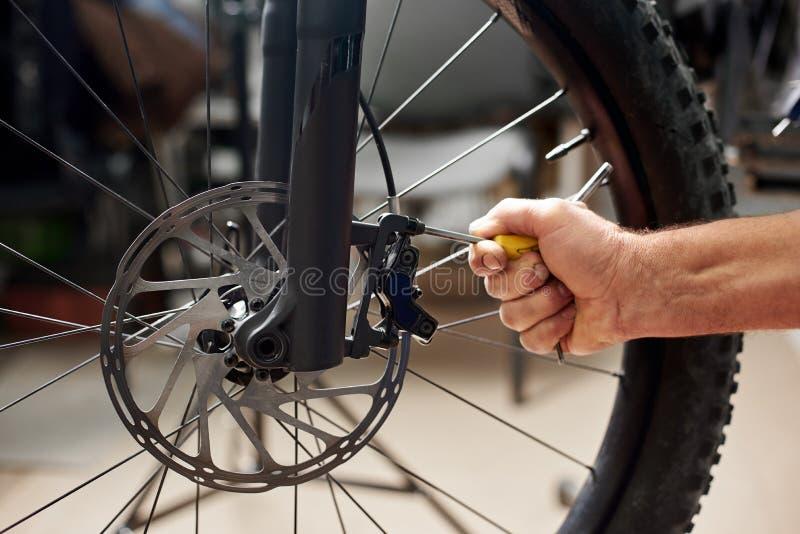 Мужской механик работая в ремонтной мастерской велосипеда используя инструменты стоковая фотография