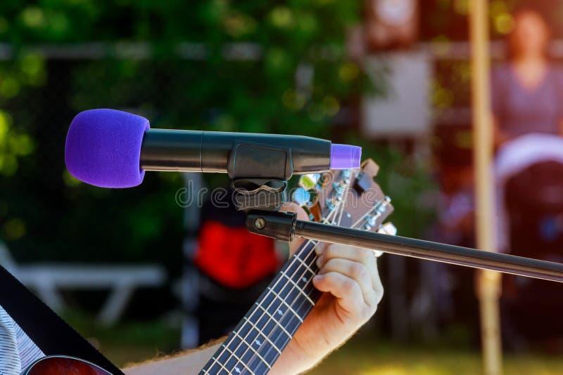 мужской музыкант играя акустическую гитару за микрофоном конденсатора в записи стоковые фотографии rf