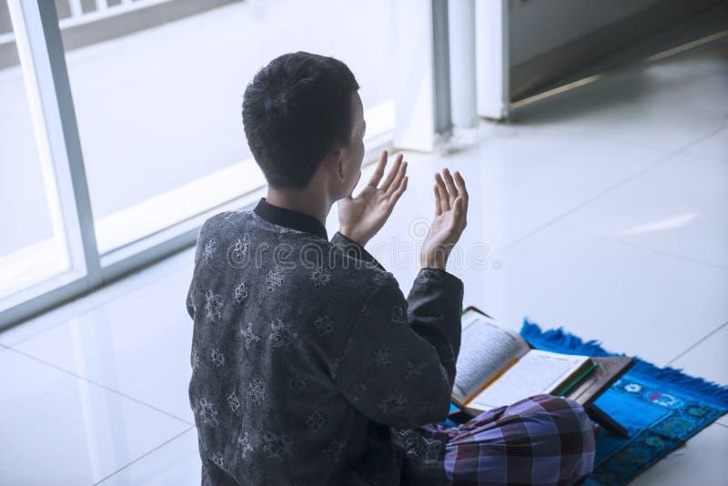 Мужской мусульманин молит к БОГУ после читая Корана стоковое фото