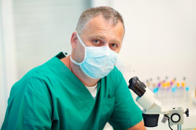 Мужской научный исследователь используя микроскоп в лаборатории стоковые изображения rf