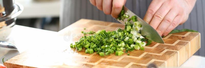 Мужской нож владением повара руки и отрезать зеленый лук стоковые фотографии rf