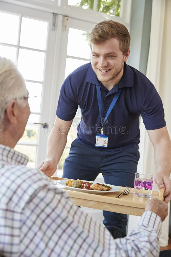 Мужской обедающий сервировки работника заботы к старшему человеку на его доме стоковое фото rf